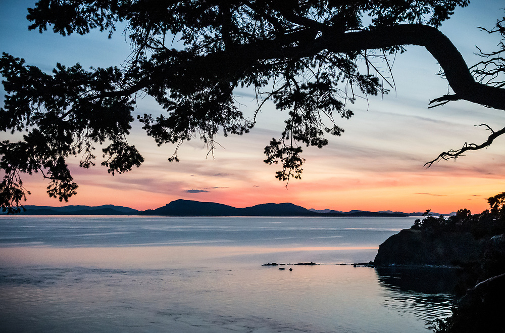 A view from near Fox cove on Sucia Island at sunset in the San Juan Islands, Washington, USA. The distant islands are mostly in BC Canada and are the Gulf Islands.