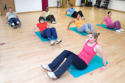 Group of adults doing floor exercising in an aerobics class at their sports leisure centre,