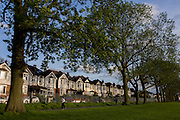 Looking up towards majestically tall Ash trees and blue skies, in an Edwardian age semi-detached house on Ruskin Park, Denmark Hill, SE24 (its post code) South London England. It is a beautiful winter afternoon in this inner-city suburban district of Britain's capital, approximately 5 miles south from the River Thames. A jogger runs past  the elegant line of period homes that were completed in 1908, the age of innovative building in the new 20th Century. The properties overlook the borough park named after John Ruskin, the renowned artist and commentator who lived in nearby Herne Hill. It looks an affluent area, a prosperous location to invest in a mortgage in uncertain times with market prices falling during the credit crunch and recession.