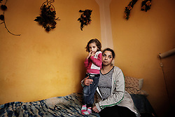 "Denisa Bandyová holds her daughter Samantha Bandyová, 4, inside their home in Ostrava, Czech Republic on March 2, 2012. Denisa was one of 18 Roma children who were represented in the D.H. and Others v. Czech Republic case, the first challenge to systemic racial segregation in education to reach the European Court of Human Rights. When this case was first brought in 2000, Roma children in the Czech Republic were 27 times more likely to be placed in ""special schools,"" intended for the mentally disabled, than non-Roma children. In 2007, the Grand Chamber of the European Court of Human Rights ruled that this pattern of segregation violated nondiscrimination protections in the European Convention on Human Rights. Despite this landmark decision, little change has occurred: the ""special schools"" have been renamed but follow the same substandard curriculum and Roma continue to be assigned to these schools in disproportionate numbers. The process of integration has barely begun."