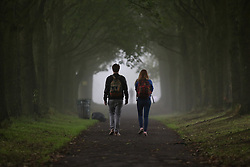 © Licensed to London News Pictures. 15/07/2016. Leeds, UK. Commuters walk through Hyde Park on a foggy autumn morning in Leeds, West Yorkshire. The start of the month has seen temperatures reach the highest they have been in the UK during September since 1911. Photo credit : Ian Hinchliffe/LNP