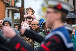 © Licensed to London News Pictures. 11/11/2018. Doncaster UK. A little girl applauds as the parade leaves the Service of remembrance at the Cenotaph in Doncaster to mark the 100th anniversary of the end of the First World War. Photo credit: Andrew McCaren/LNP