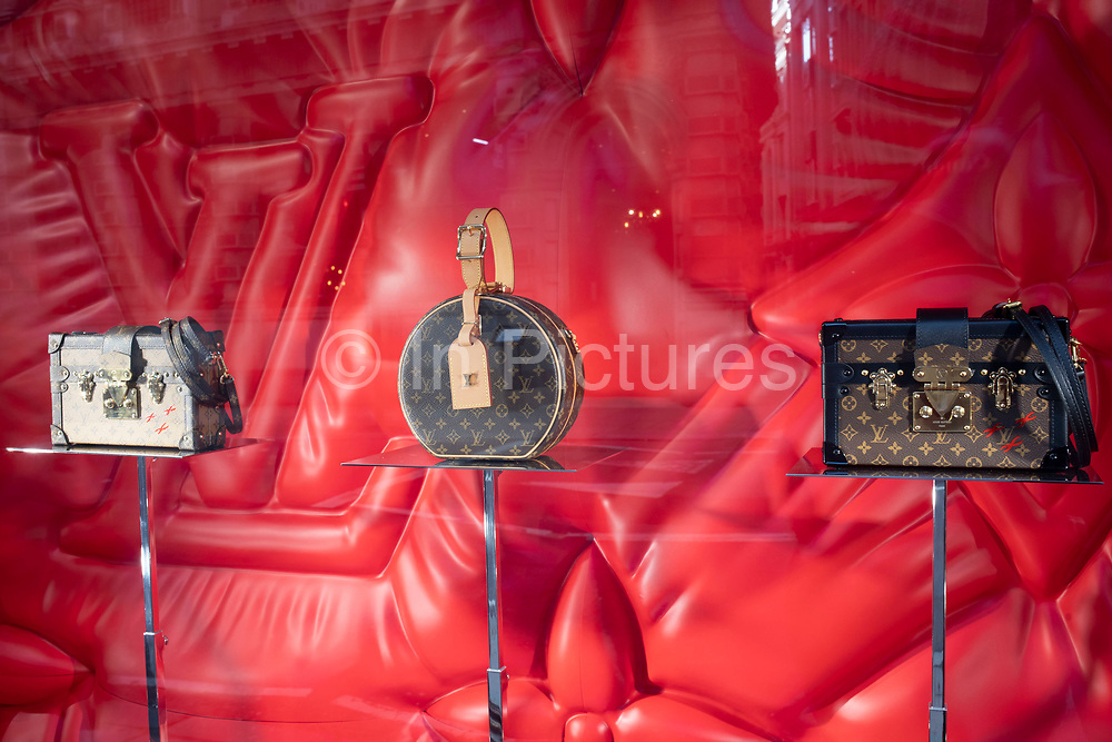 Bag in the shop window of Louis Vuitton store in the City of London on 28th January 2020 in London, England, United Kingdom. Louis Vuitton Malletier, commonly referred to as Louis Vuitton or shortened to LV, is a French fashion house founded in 1854 by Louis Vuitton. The labels LV monogram appears on most of its products, ranging from luxury trunks and leather goods to ready-to-wear, shoes, watches, jewelry, accessories, sunglasses, and books.