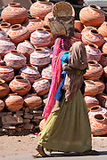 Indian woman out shopping carrying child walks past clay water pots on sale in old town Udaipur, Rajasthan, Western India,