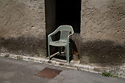 Plastic garden chair in a doorway in Termes, France. Termes is a commune in the Aude department in southern France.