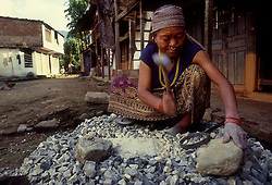 POKHARA, NEPAL - OCTOBER 1992 - A Nepalese woman earns pennies a day breaking rocks with a hammer near her home in Pokhara, Nepal. Women's rights have been a controversial issue in Nepalese society, where women don't enjoy the same rights that men do, such as the right to own land. (PHOTO © JOCK FISTICK)