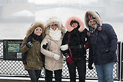 A group of tourists pose for a photograph near the Tower of London during snow fall in London, England on March 2nd, 2018 as freezing weather conditions dubbed the Beast from the East combined with Storm Emma have brought snow and freezing weather to the UK.