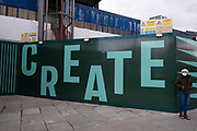 People pass a hoarding with the word create surrounding the now closed down Elephant and Castle shopping centre which is due for demolition on 5th March 2021 in London, United Kingdom. The area is now subject to a master-planned redevelopment budgeted at £1.5 billion. A Development Framework was approved by Southwark Council in 2004. It covers 170 acres and envisages restoring the Elephant to the role of major urban hub for inner South London.