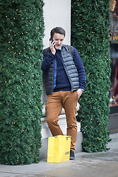 © Licensed to London News Pictures. 22/12/2017. London, UK. A man with a shopping bag speaks on a mobile phone in Oxford Street in London on the last Friday before Christmas. Photo credit: Vickie Flores/LNP