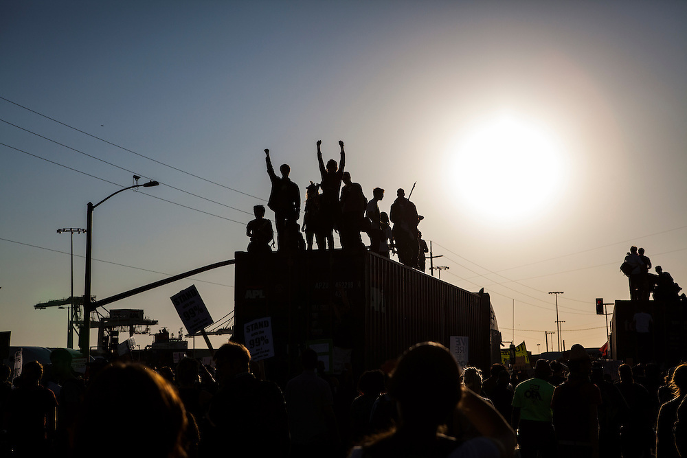 OAKLAND, CA - NOVEMBER 2, 2011: Occupy Oakland protesters exalt after they climb on top of a tractor trailer during their shutdown of the Port of Oakland.