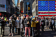 Groups of tourists look up to see their photos appear on the large digital screen in Times Square Midtown Manhattan, New York City, New York, United States.   Behind them is a large screen of the large American Flag on the side of the US Armed Forces Recruiting Station.