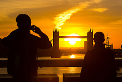 © Licensed to London News Pictures. 25/10/2015. London, UK. People watch the sunrise behind Tower Bridge on the River Thames in London this morning. The skies are clear and the weather is much colder than yesterday in London for the first autumn morning after the clocks went back and UK time returns to Greenwich Mean Time (GMT) and officially marks the end of British Summer Time (BST).Photo credit : Vickie Flores/LNP