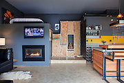 Jen and Bryn Scott of Zen Box Design are the proud designers and owners of 460 square feet with a Nanawall folding glass wall, DIY rolling doors, a wood counter that rolls out into a table, concrete coutner tops, a four burner gas stove, a two pot dish washer, various reclaimed wood (mostly Fir) cabinets, oriented strand board floors, a gas fireplace and a spcasious conrete bathroom with a sky light. Their dog Karma enjoys the heat from the fire. <br /> Image by Shauna Intelisano