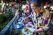 13 JANUARY 2013 - BANGKOK, THAILAND:  A woman serves green curry on rice noodles in a cafe in the Bang Luang neighborhood. The Bang Luang neighborhood lines Khlong (Canal) Bang Luang in the Thonburi section of Bangkok on the west side of Chao Phraya River. It was established in the late 18th Century by King Taksin the Great after the Burmese sacked the Siamese capital of Ayutthaya. The neighborhood, like most of Thonburi, is relatively undeveloped and still criss crossed by the canals which once made Bangkok famous. It's now a popular day trip from central Bangkok and offers a glimpse into what the city used to be like.     PHOTO BY JACK KURTZ