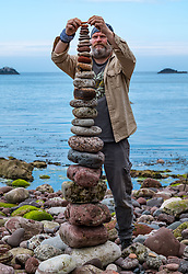 Dunbar, East Lothian, Scotland, United Kingdom 10 July 2021. European Stone Stacking Championship: The first day of the event, which is part of the Edinburgh Science Festival.  Pictured: James Brunt, from Yorkshire, competes in the most stones stacked in half an hour competition. The record is 42.<br /> Sally Anderson | EdinburghElitemedia.co.uk