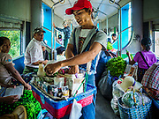 25 NOVEMBER 2017 - YANGON, MYANMAR: A betel vendor on the Yangon Circular Train. The Yangon Circular Train is a 45.9-kilometre (28.5 mi) 39-station two track loop system connects satellite towns and suburban areas to downtown. The train was built during the British colonial period, the second track was built in 1954. Trains currently run both directions (clockwise and counter-clockwise) around the city. The trains are the least expensive way to get across Yangon and they are very popular with Yangon's working class. About 100,000 people ride the train every day. A a ticket costs 200 Kyat (about .17¢ US) for the entire 28.5 mile loop.    PHOTO BY JACK KURTZ