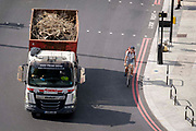Seen from the elevation from the Marble Arch Mound, a cyclist turns left on the inside of a waste company lorry, on 11th August 2021, in London, England.