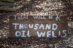 © Licensed to London News Pictures. 02/03/2017. Coldharbour, UK. A sign near the 'Protection Camp' on Leith Hill says 'THERE WILL BE A THOUSAND OIL WELLS' . Activists have constructed and occupied a fort and some trees on the site of a proposed oil well. Planning permission for 18 weeks of exploratory drilling was granted to Europa Oil and Gas in August 2015 after a four-year planning battle. The camp was set up by protestors in October 2016 in order to draw  attention to plans to drill in this Area of Outstanding Natural Beauty (AONB) in the Surrey Hills. The camp has received support from the local community.  Photo credit: Peter Macdiarmid/LNP