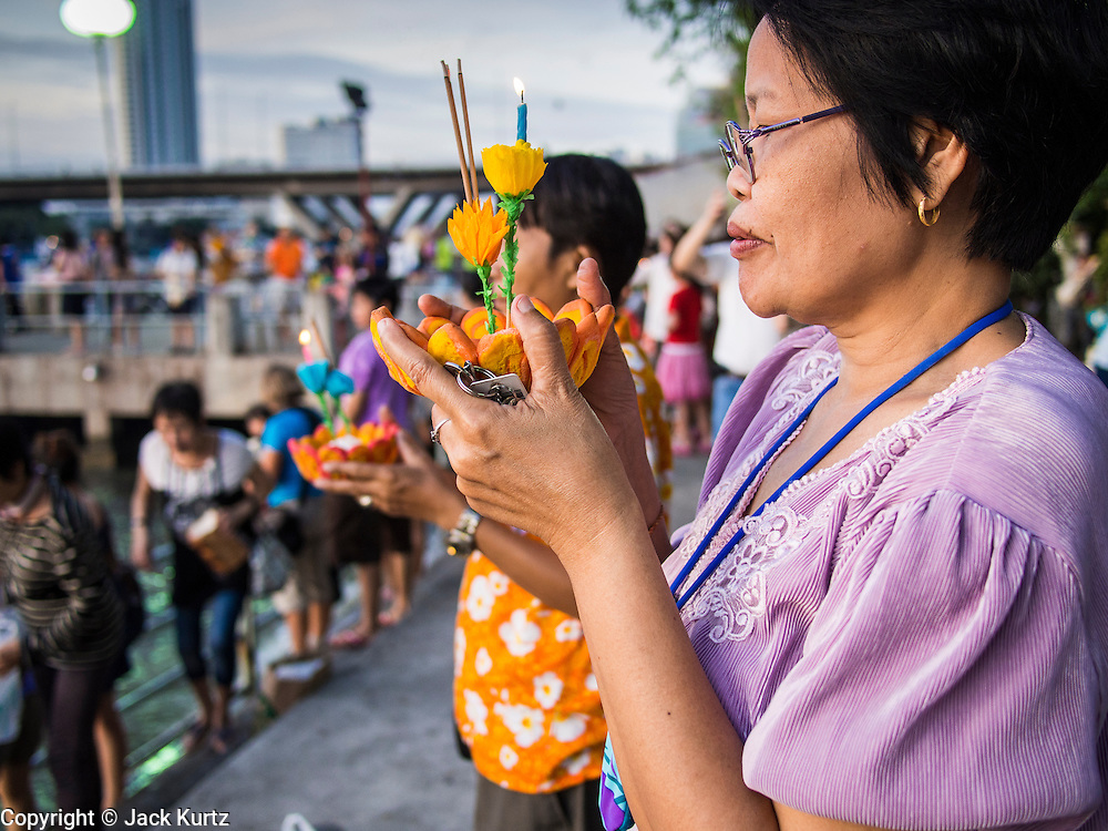 """17 NOVEMBER 2013 - BANGKOK, THAILAND: A woman prays before floating her krathong in the Chao Phraya River near Wat Yannawa in Bangkok. Loy Krathong (also written as Loi Krathong) is celebrated annually throughout Thailand and certain parts of Laos and Burma (in Shan State). The name could be translated """"Floating Crown"""" or """"Floating Decoration"""" and comes from the tradition of making buoyant decorations which are then floated on a river. Loi Krathong takes place on the evening of the full moon of the 12th month in the traditional and they do this all evening on the 12th month Thai lunar calendar. In the western calendar this usually falls in November. The candle venerates the Buddha with light, while the krathong's floating symbolizes letting go of all one's hatred, anger, and defilements       PHOTO BY JACK KURTZ"""