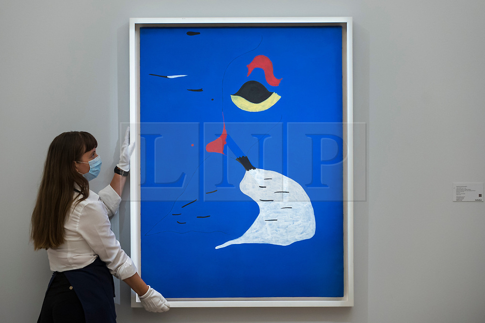 """© Licensed to London News Pictures. 23/07/2020. LONDON, UK.  A technician presents """"Peinture (Femme au chapeau rouge) (1927) by Joan Miró, estimate: £20-30 million. Preview of works on display at Sotheby's London ahead of a one-off auction on July 28.  Titled 'Rembrandt to Richter', the sale will offer the very best from Old Masters, Impressionist & Modern Art, Modern & Post-War British Art and Contemporary Art.  The exhibition is open to the public at Sotheby's New Bond Street galleries until July 28. [Image embargoed for release until 9am BST 24 July 2020].  Photo credit: Stephen Chung/LNP"""