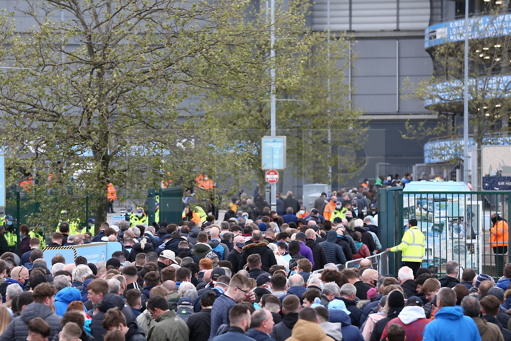 © Licensed to London News Pictures. 23/05/2021. Manchester, UK.  Manchester City fans queue to enter the Etihad on the final day of the season. Thousands of supporters have gathered at the Etihad Stadium to celebrate winning their 5th Premier League title in 10 years.  Photo credit: Adam Vaughan/LNP