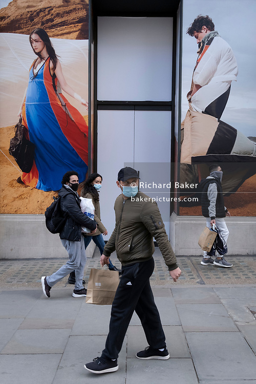On the day that the UK government eased Covid restrictions to allow non-essential businesses such as shops, pubs, bars, gyms and hairdressers to re-open, shoppers walk past a fashion hoarding on Regent Street, on 12th April 2021, in London, England.
