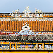 A colorful roof at the Imperial City in Hue, Vietnam. A self-enclosed and fortified palace, the complex includes the Purple Forbidden City, which was the inner sanctum of the imperial household, as well as temples, courtyards, gardens, and other buildings. Much of the Imperial City was damaged or destroyed during the Vietnam War. It is now designated as a UNESCO World Heritage site.