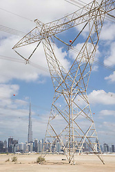 Skyline of Dubai with high-voltage electricity transmission pylons in United Arab Emirates