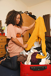 Young black woman unpacking a suitcase.
