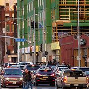 Pedestrian crosswalk among car traffic along 20th Street at Main, Kansas City, Missouri. Hilton Home2Suites location under construction at corner.