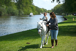 © London News Pictures. 15/05/2016. Windsor, UK. One year old Matilda Burnett with her mother Natalie Burnett,  riding their horse Arrow, on the final day of the 2016 Royal Windsor Horse Show, held in the grounds of Windsor Castle in Berkshire, England. This years event is part of HRH Queen Elizabeth II's 90th birthday celebrations.  Photo credit: Ben Cawthra/LNP