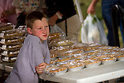 Trevan Doland stands watch over the many miniature pies of Doughland Bakery at the Grinnell Farmers' Market on Thursday.