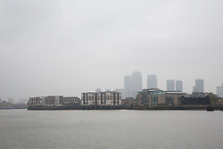 © Licensed to London News Pictures. 04/04/2014. London, UK. Smog continues to shroud the Canary Wharf financial district in London this morning, 4th April 2014. Weather forecasters predict pollution levels have peaked in London and that a westerly wind today will start to blow the smog away into the North Sea and clear the air. Photo credit : Vickie Flores/LNP