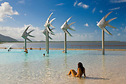 Young woman sunbathes in the Cairns Esplanade Lagoon, a waterpark in Queensland