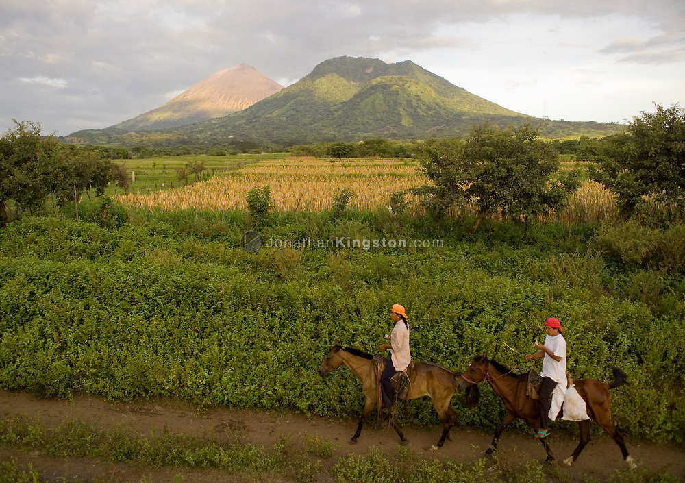 """Two men ride horses along a trail with part of the San Cristobal volcanic complex in the background, Chinandega Nicaragua. Nicaragua is often referred to as the """"Land of Lakes and Volcanoes."""" The area is rich with wildlife, flora and fauna, and there are large areas of preserved land."""