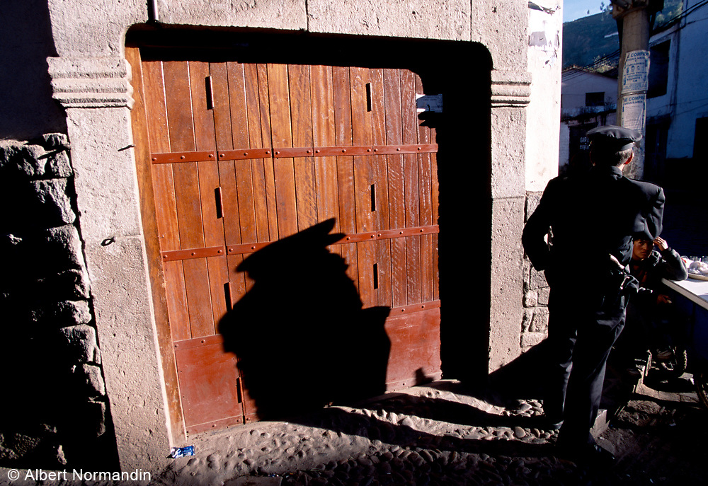 Police officer with long shadow in old city