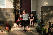 Kyla Hill, 5, (left), Becky Hill, (center), and Kaden Hill, 7, (right) pose for a portrait at their home in Chico, Calif. on Thursday July 23, 2020. Rebecca has to balance what's best for her children's education with their safety and that of her immuno-compromised husband. Photo by Salgu Wissmath for CalMatters