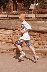 Young man jogging along pavement,