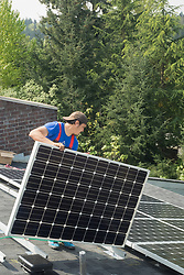 North America, United States, Washington, Bellevue, installation of solar panels on roof of house.  MR  PR