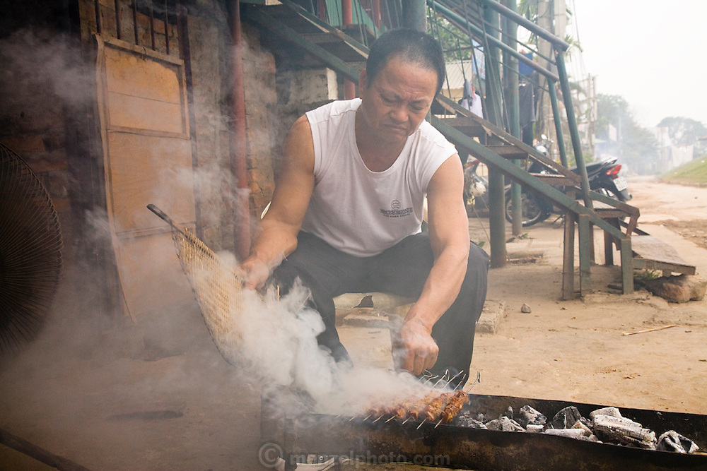 A man grills dog meat in the Pho Nghi Tam area of Hanoi, Vietnam.