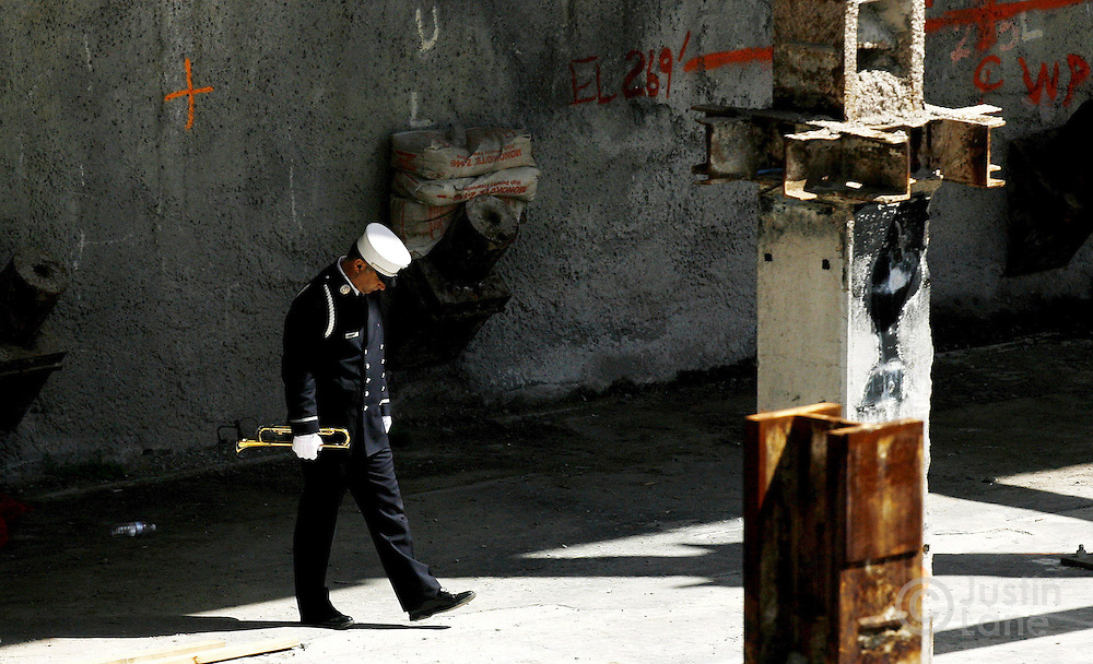 A New York City Fire Department bugler walks to the edge of the World Trade Center site to play taps at the close of the September 11th commemoration ceremony in New York on Monday 11 September 2006.