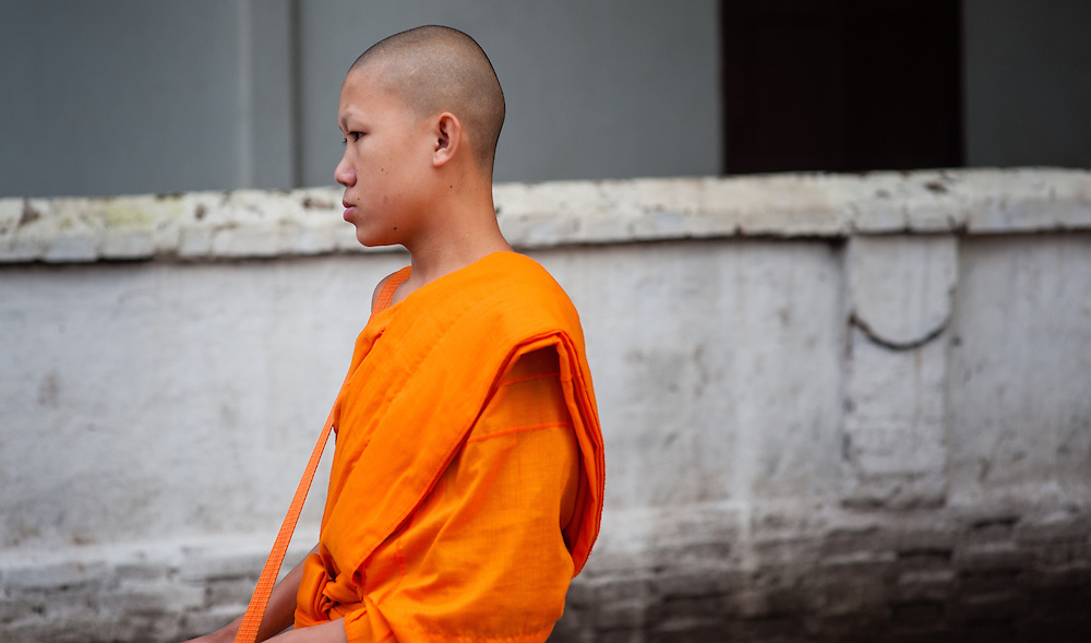 Buddhist monk after receiving daily alms at dawn in Luang Prabang (Laos).