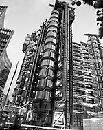 Lloyds Bank Tower at number One Lime Street. In this image we have a black and white photograph of the famous Lloyds Building by Richard Rogers. We see the building through some of the trees that surround it showing how it has managed to squeeze into the compacted space of the city of London. <br /> <br /> The added depth and texture which can only be achieved in black and white photography has been used to great effect to show off this amazing architectural landmark. Once we remove the bright colours used to illuminate this building we are allowed to enjoy the simplicity and form of the architects design and appreciate why this such an important building in the London landscape.