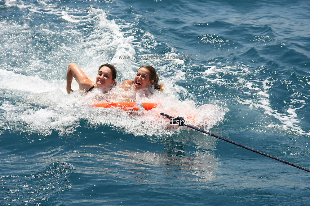 four women in their 20s and 30s having fun in the water holding onto a life saver buoy while being pulled by a boat