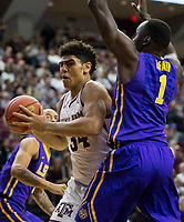 Texas A&M center Tyler Davis (34) drives in on LSU forward Duop Reath (1) during the first half of an NCAA college basketball game Saturday, Jan. 6, 2018, in College Station, Texas. (AP Photo/Sam Craft)