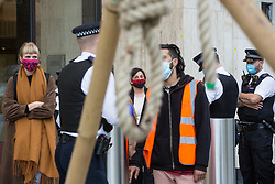 London, UK. 10th November, 2020. An environmental activist from Extinction Rebellion is pictured through a noose prior to her arrest by Metropolitan Police officers following a protest outside the Shell Centre to mark the 25th anniversary of the killings of the Ogoni Nine. The Ogoni Nine, leaders of the Movement for the Survival of the Ogoni People (MOSOP) including activist Ken Saro-Wiwa, were executed by the Nigerian government in 1995 after having led a series of peaceful marches involving an estimated 300,000 Ogoni people against the environmental degradation of the land and waters of Ogoniland by Shell and to demand both a share of oil revenue and greater political autonomy.