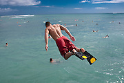 A young man with swim fins jumps off a pier in Hawaii and is airborne.