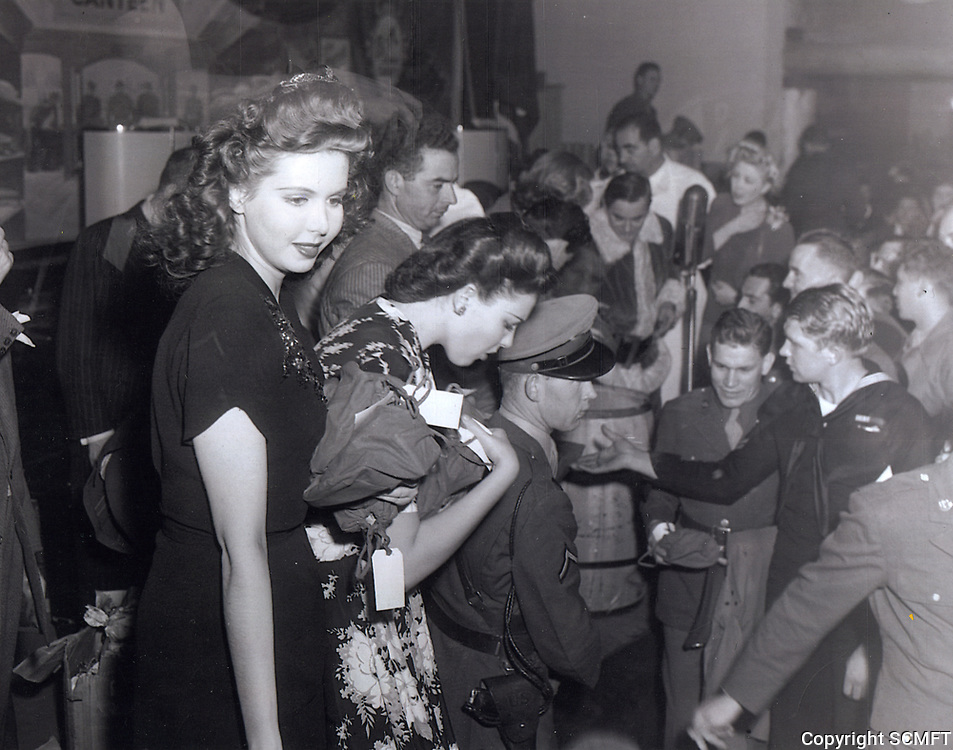 12/25/43 Ann Miller and Linda Darnell hand out Christmas presents at the Hollywood Canteen