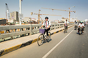 """30 JANUARY 2013 - PHNOM PENH, CAMBODIA: Missionaries from the Church of Latter Day Saints (Mormons) peddle their bikes across a bridge in Phnom Penh, Cambodia. It is customary for Mormon youth to go on a 2 year """"mission"""" to evangelize and convert others to their religion. As many 75,000 missionaries served the church outside of the US in 2011.    PHOTO BY JACK KURTZ"""