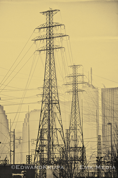 Electriciy pylons, or transmission towers, loom over city at sunset. Toronto, Ontario, Canada.